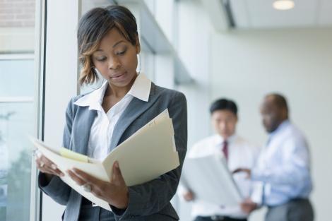 Black businesswoman looking at paperwork in folder