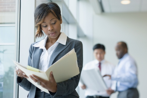 Black businesswoman looking at paperwork in folder